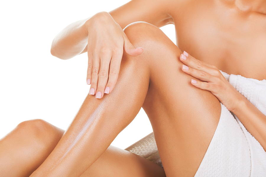 woman in towel applying oil to leg