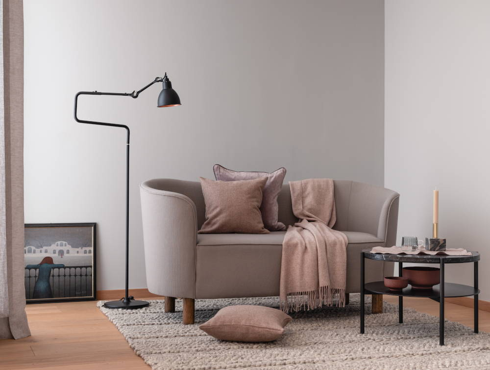 Sofa with pink cushions and blanket