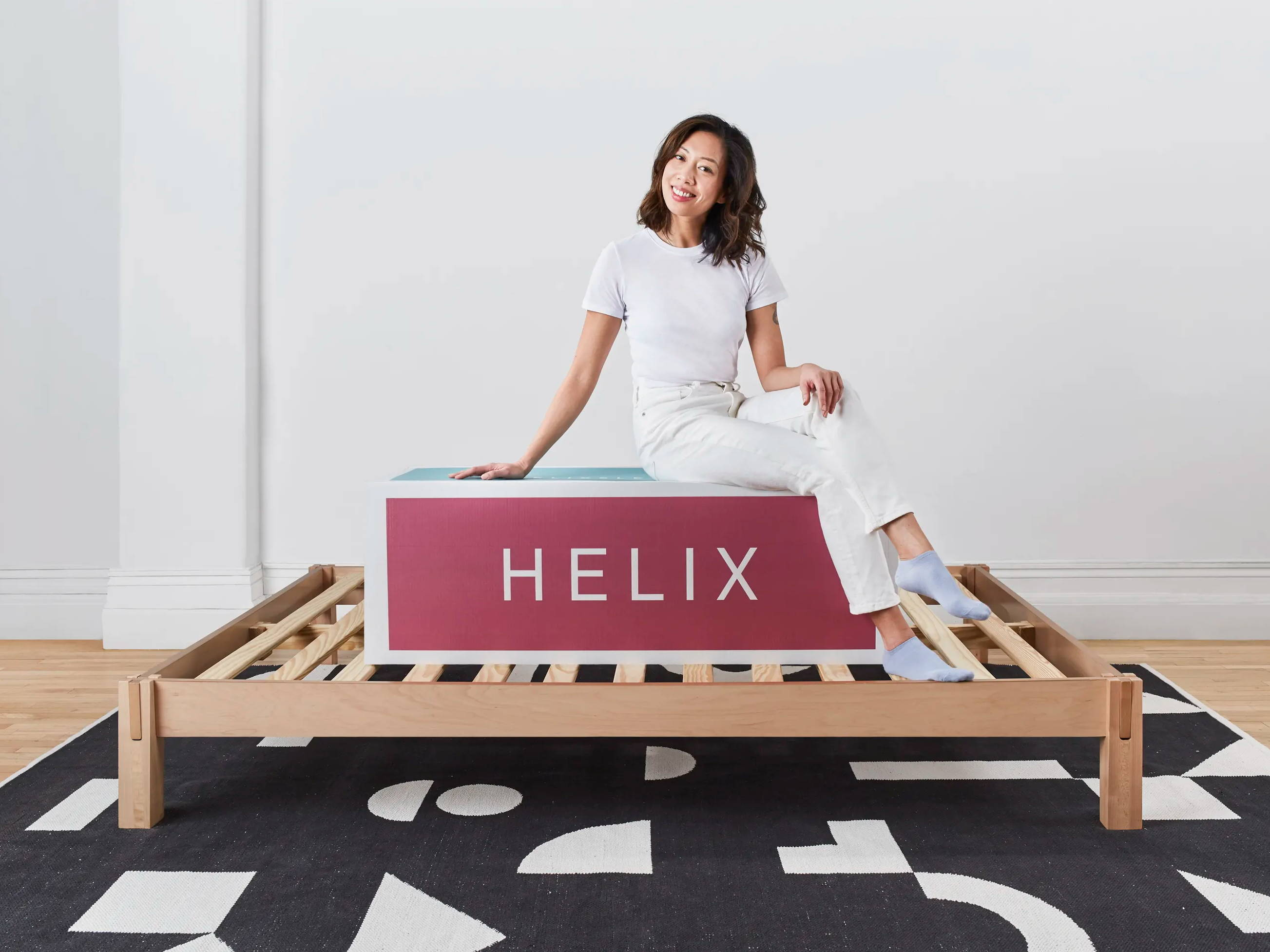 Woman sitting on Helix delivery box on top of Helix wooden frame