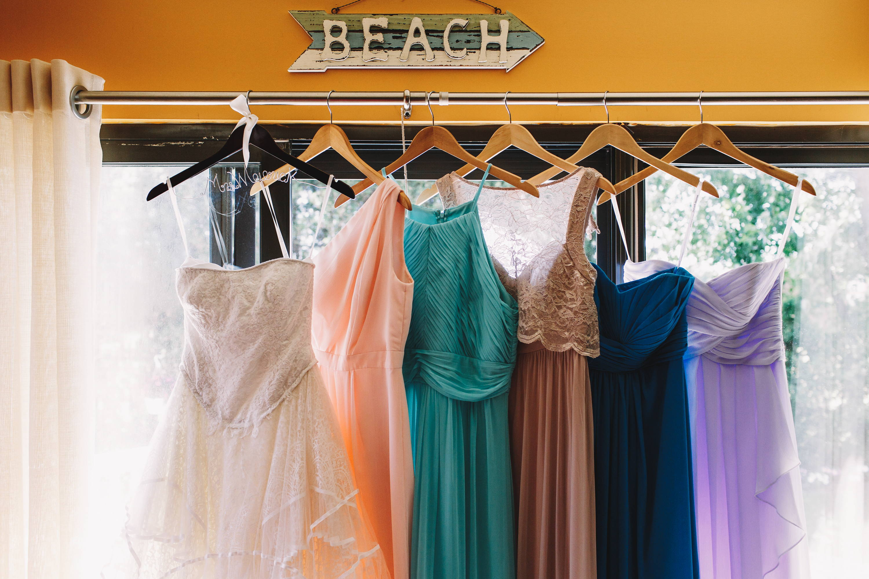 Beach sign and different colored bridesmaid dresses