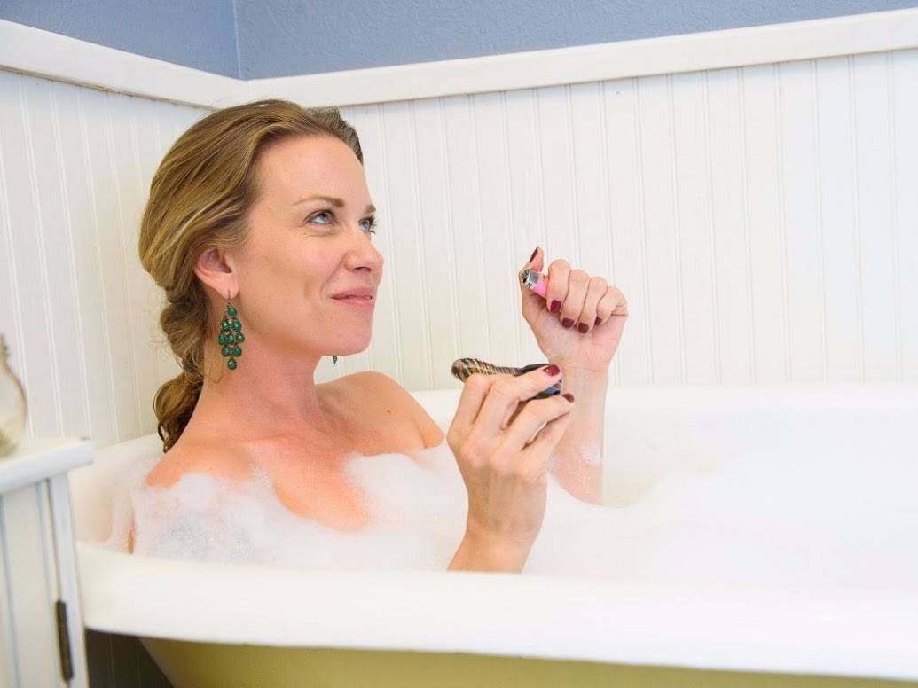 Woman in bath tub smoking DopeBoo hand pipe