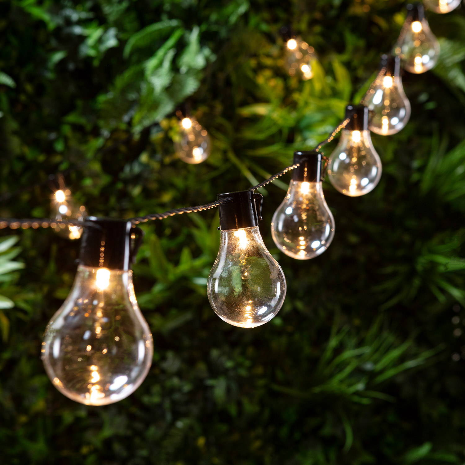 A string of warm white festoon lights in greenery
