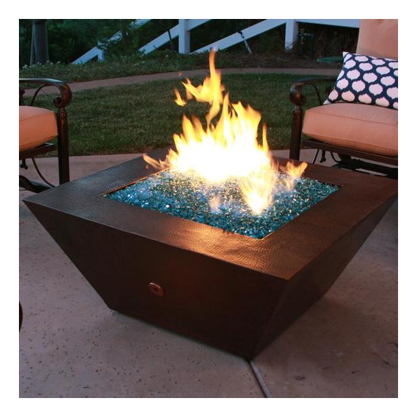 A copper fire pit ignited over a bed of glass