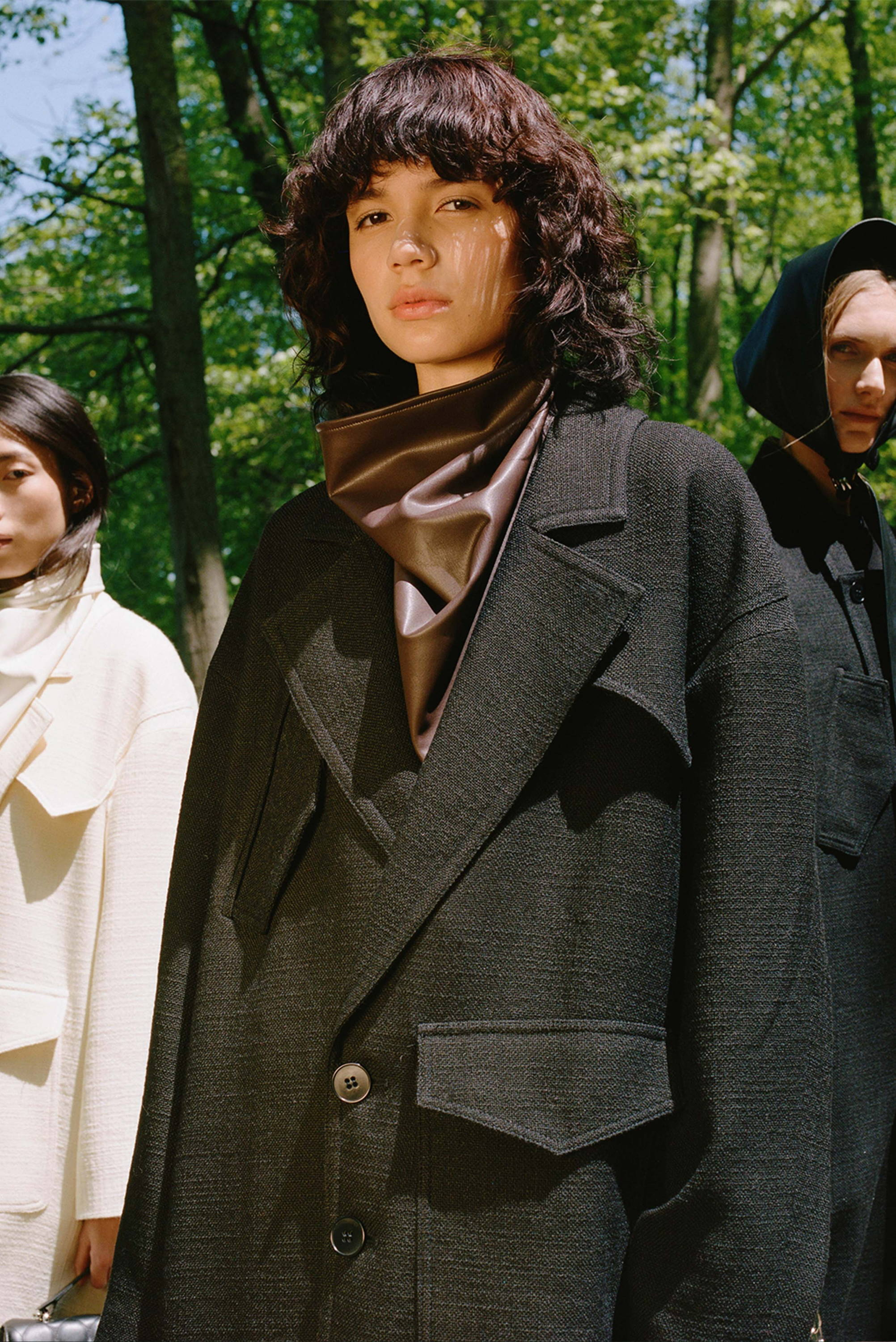 Model wearing oversized black coat with brown leather bandana.