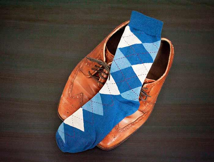 Dusty blue men's argyle dress socks displayed on a pair of brown oxfords