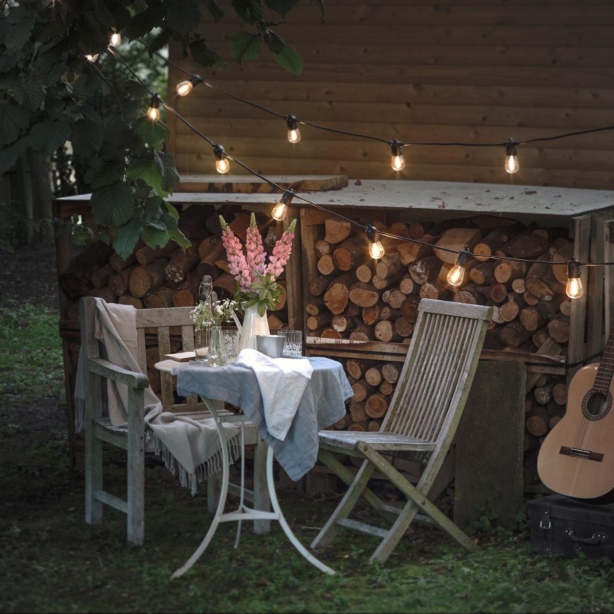 Gartenstühle mit Partylichterkette am Abend.