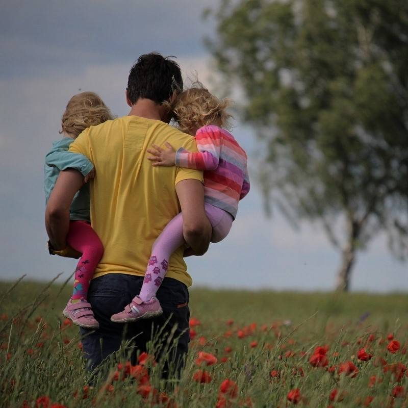 A dad walking through a field of poppies with his two daughters on his waist