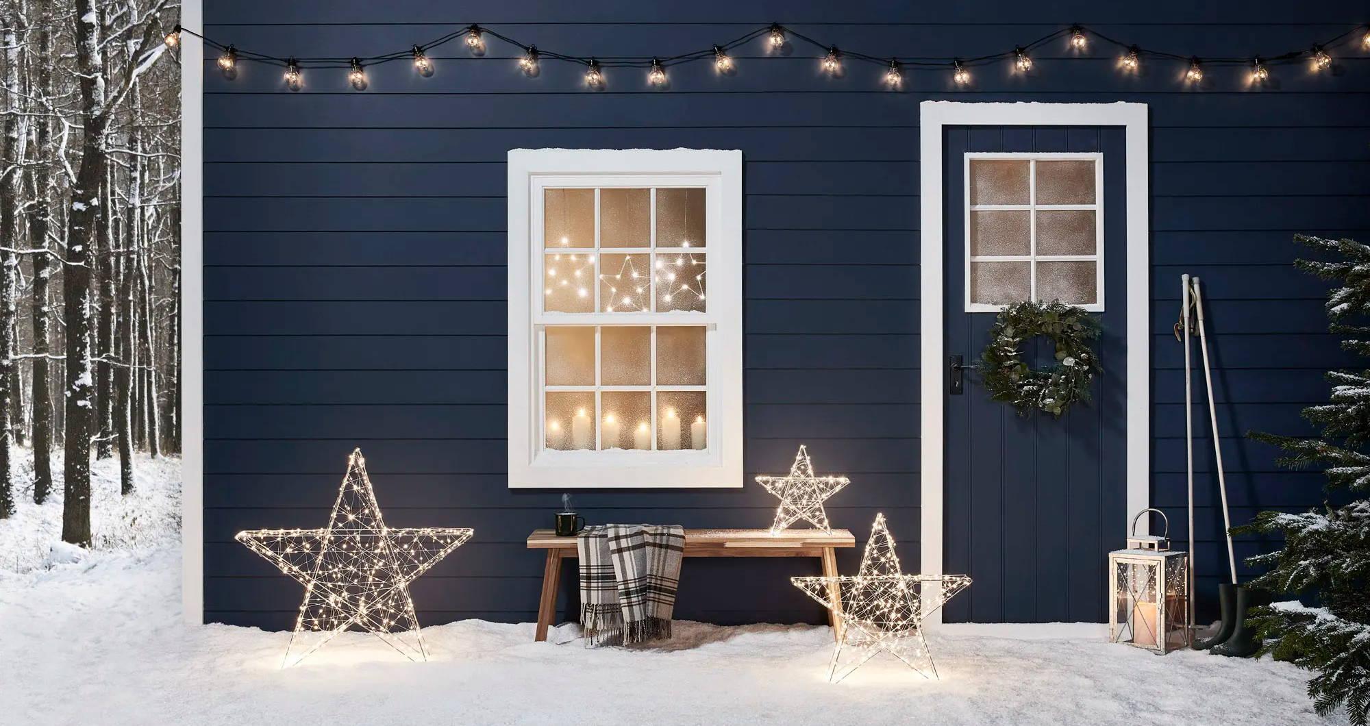 Etoiles lumineuses extérieures devant une cabane d'hiver bleue