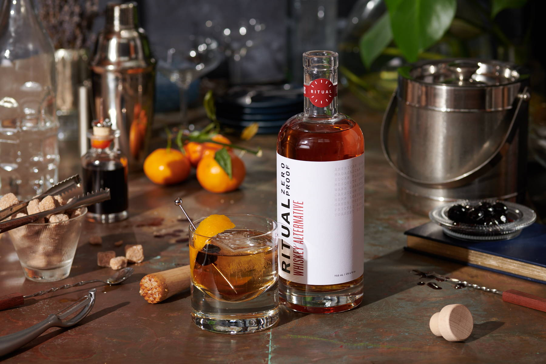A spirit-free Old Fashioned, with oranges and bar accessories, next to a bottle of Ritual non-alcoholic whiskey alternative.