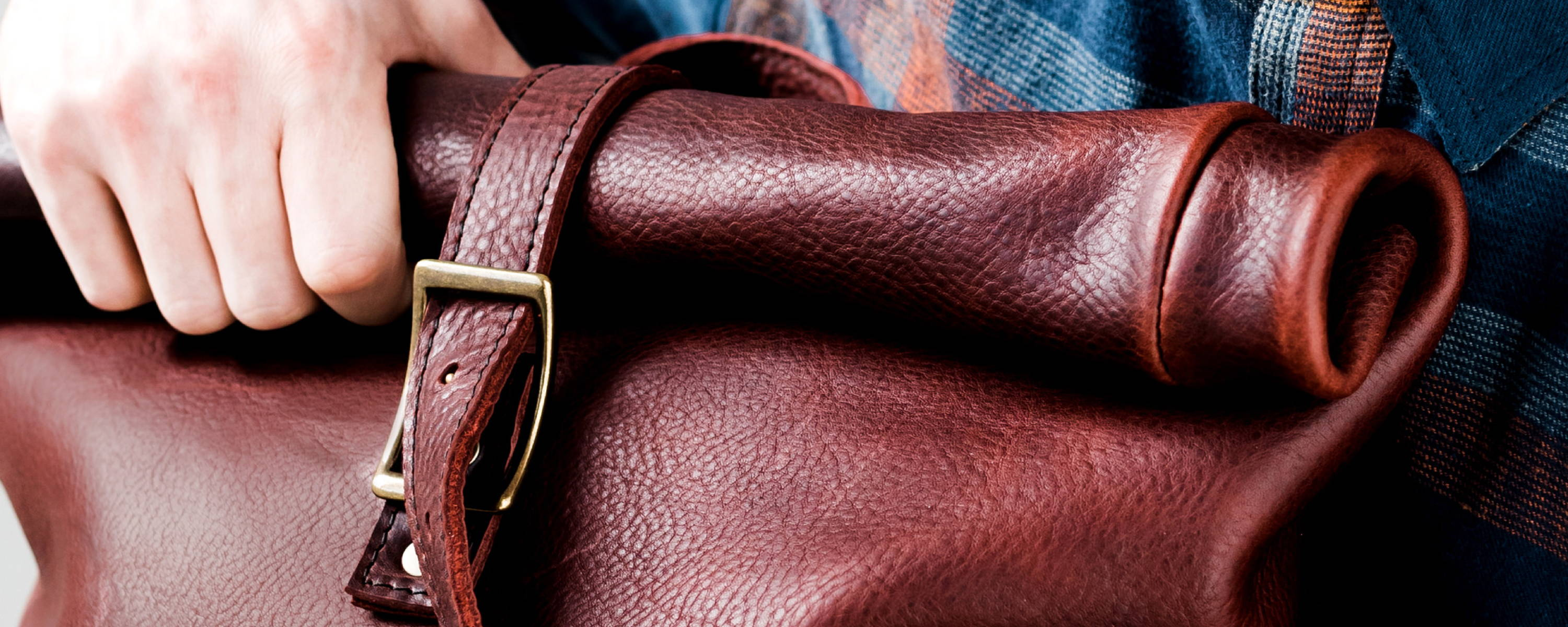 closeup photo of oxblood colored leather rolltop backpack by portland leather goods