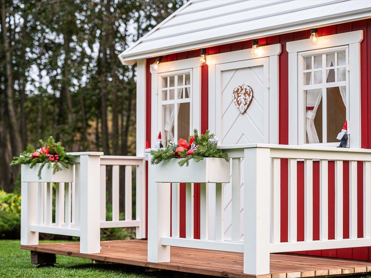 Red and white wooden playhouse with a white porch and christmas decorations with forest background by WholeWoodPlayhouses