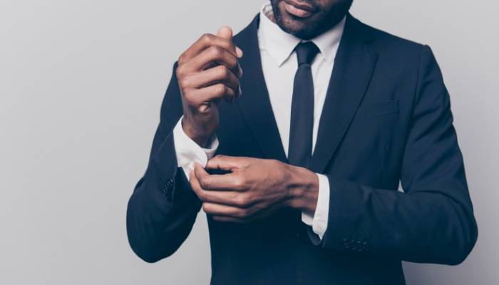 Man in suit and tie adjusting cuffs