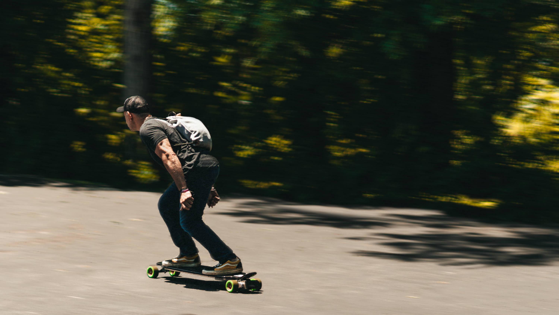 man skateboarding with light grey anti-theft drawstring backpack