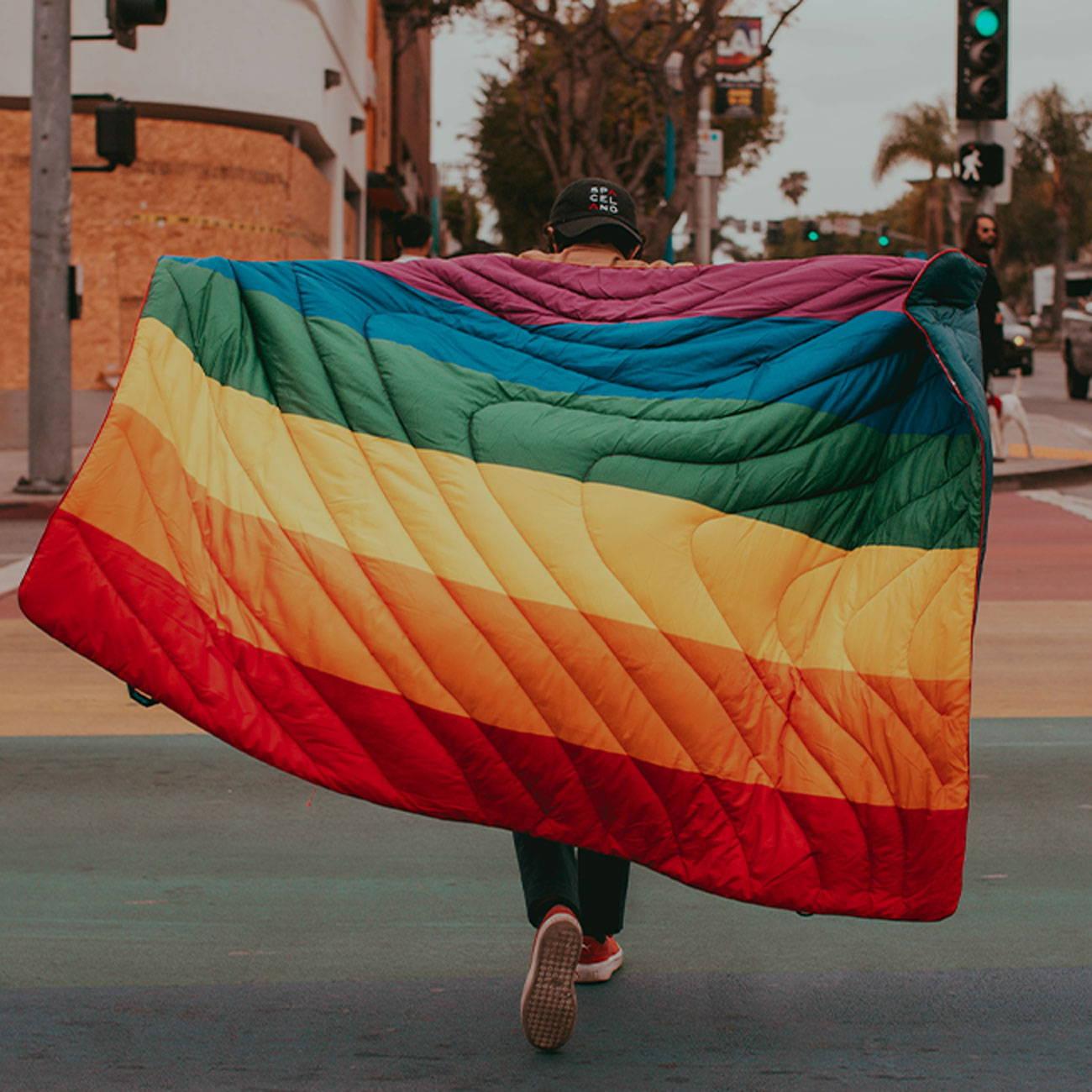 Man walking through The Castro San Francisco with rainbow pride colored Rumpl blanket