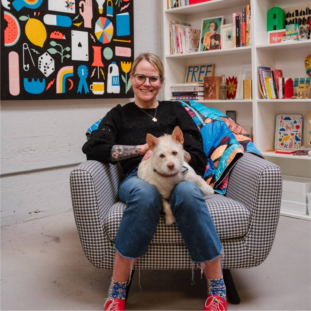 Lisa Congdon sitting in chair holding dog