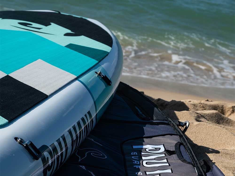 The Big EZ Hawaiian stand up paddle board ontop of a paddle board bag