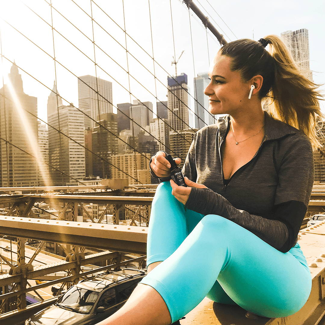 A happy Mtiva customer sitting on the Brooklyn Bridge after taking some of our Natural flavored CBD Oil.