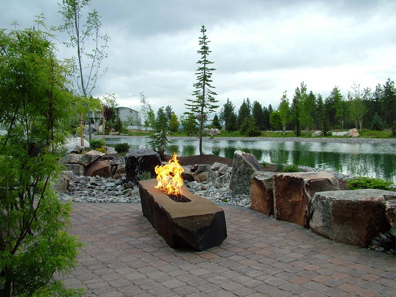 A stone fire pit ablaze next to a streaming river