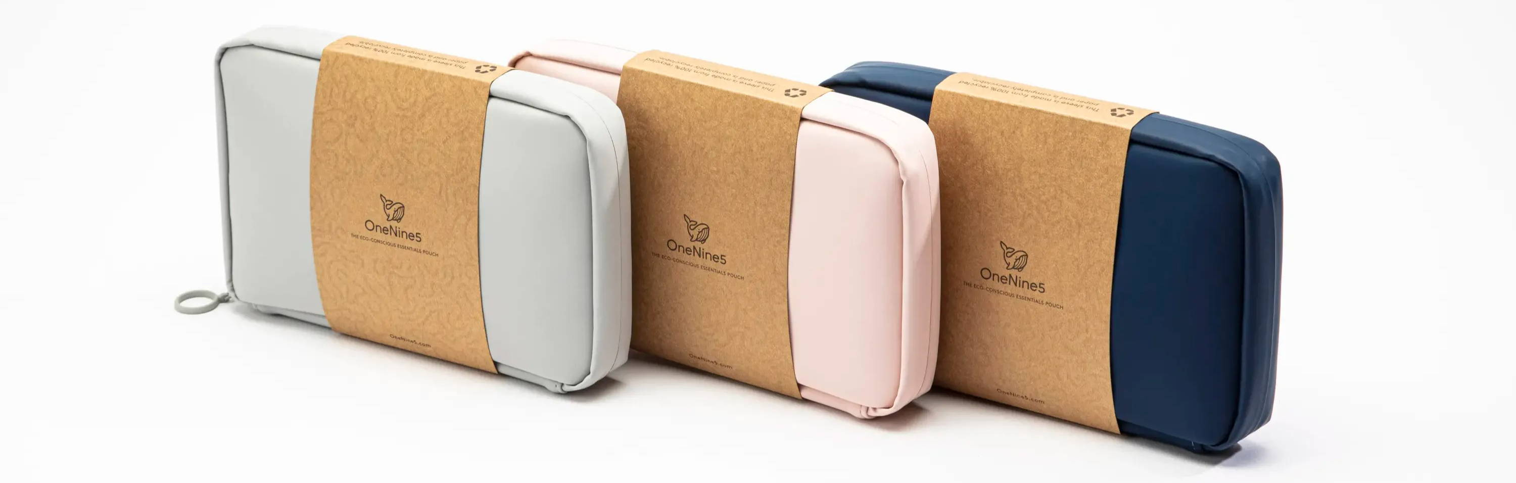 Moeraki Grey, Komodo Pink & Havelock Blue Makeup Pouch lined up on a white background. Each makeup pouch is packaged in a 100% recycled kraft paper sleeve.