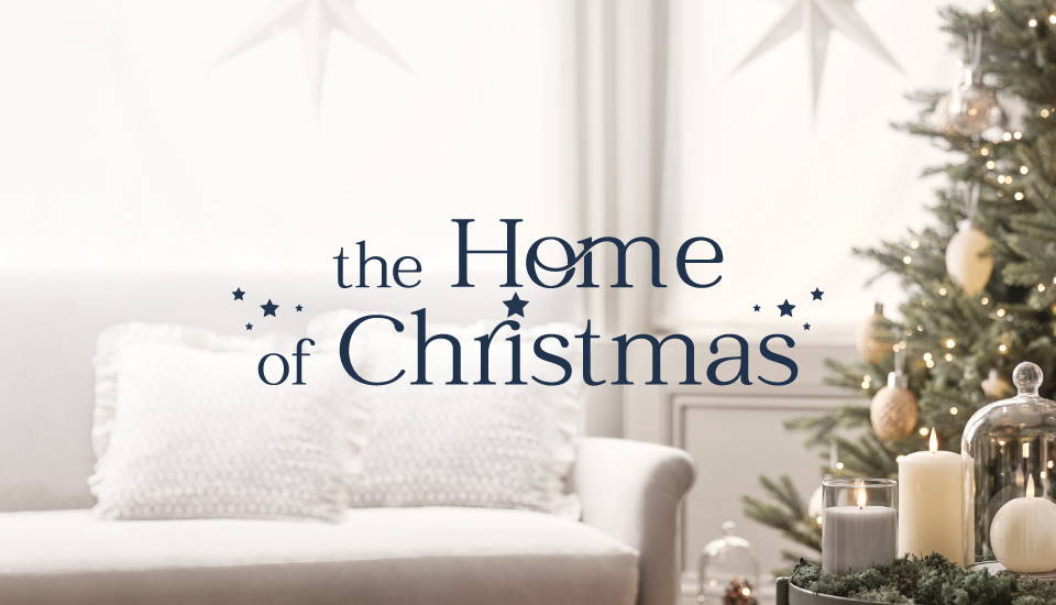 The Home of Christmas living room featuring an illuminated Christmas tree and LED candles