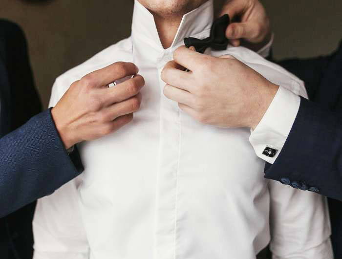Man putting on black bow tie for wedding day