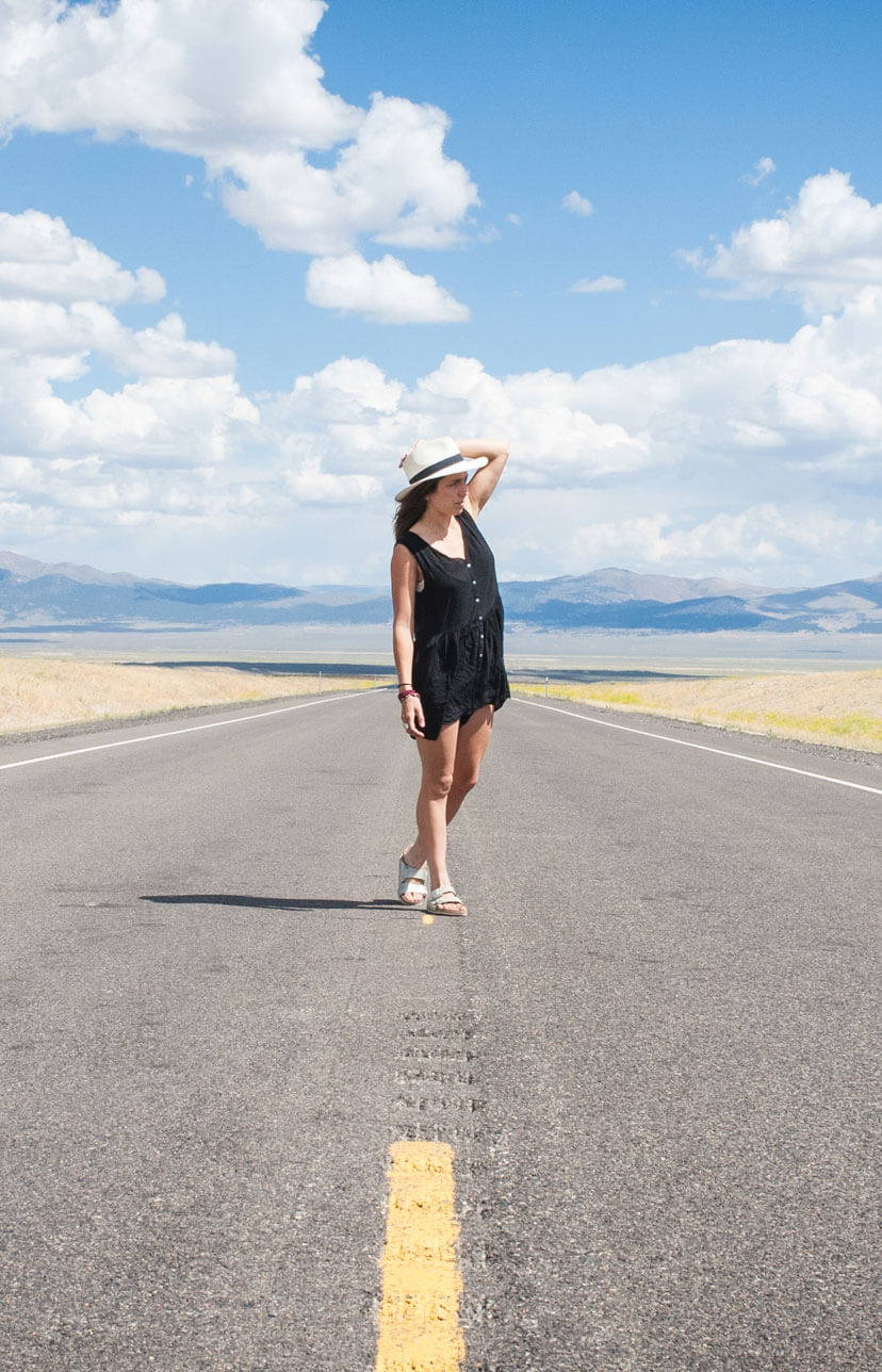 Woman wearing sun hat standing in the middle of the road with the sky and mountains behind her.