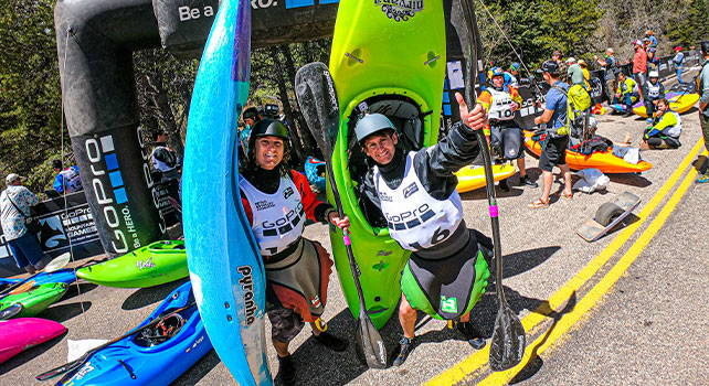 Two competitors posing with their kayaks. Photo Credit: Zach Mahone