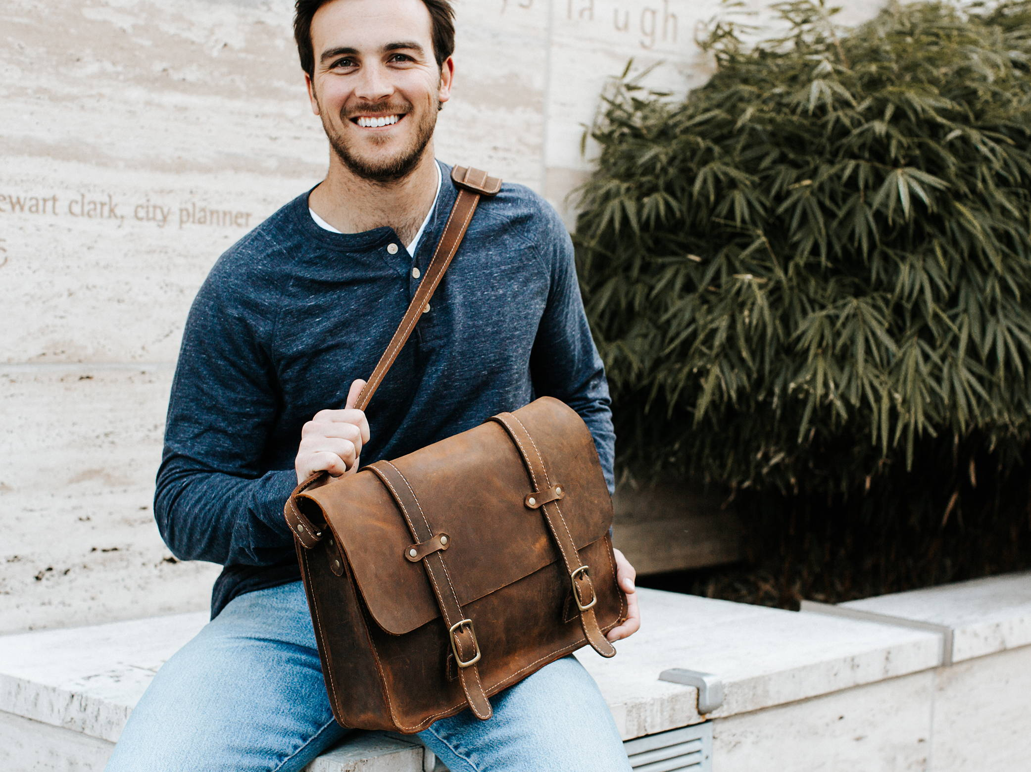 smiling man holding handmade leather messenger bag on lap
