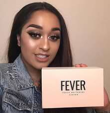 girl smiles holding Fever smile teeth whitening kit