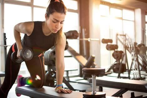 Frau macht Kurzhantelrudern im Rahmen eines Ganzkörper-Trainingsplans