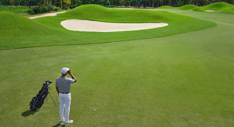 Golfer using a golf laser rangefinder onthe golf course