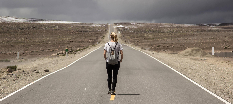 girl wearing grey lockable anti-theft bag on road trip