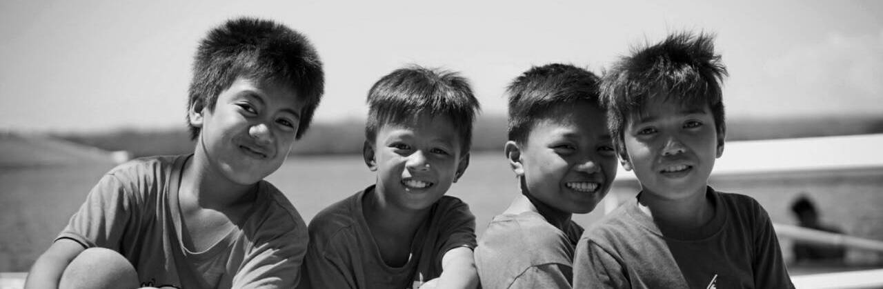 Four street kids smiling together in black and white