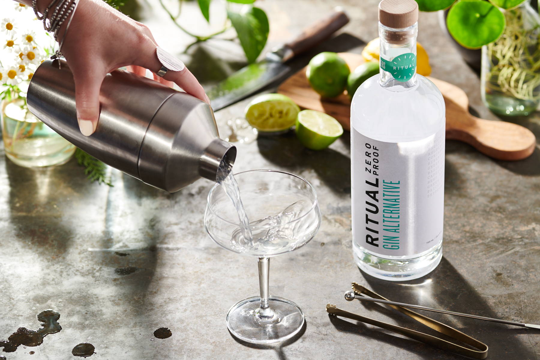 An alcohol-free martini being poured from a cocktail shaker, next to a bottle of Ritual spirit-free gin alternative.