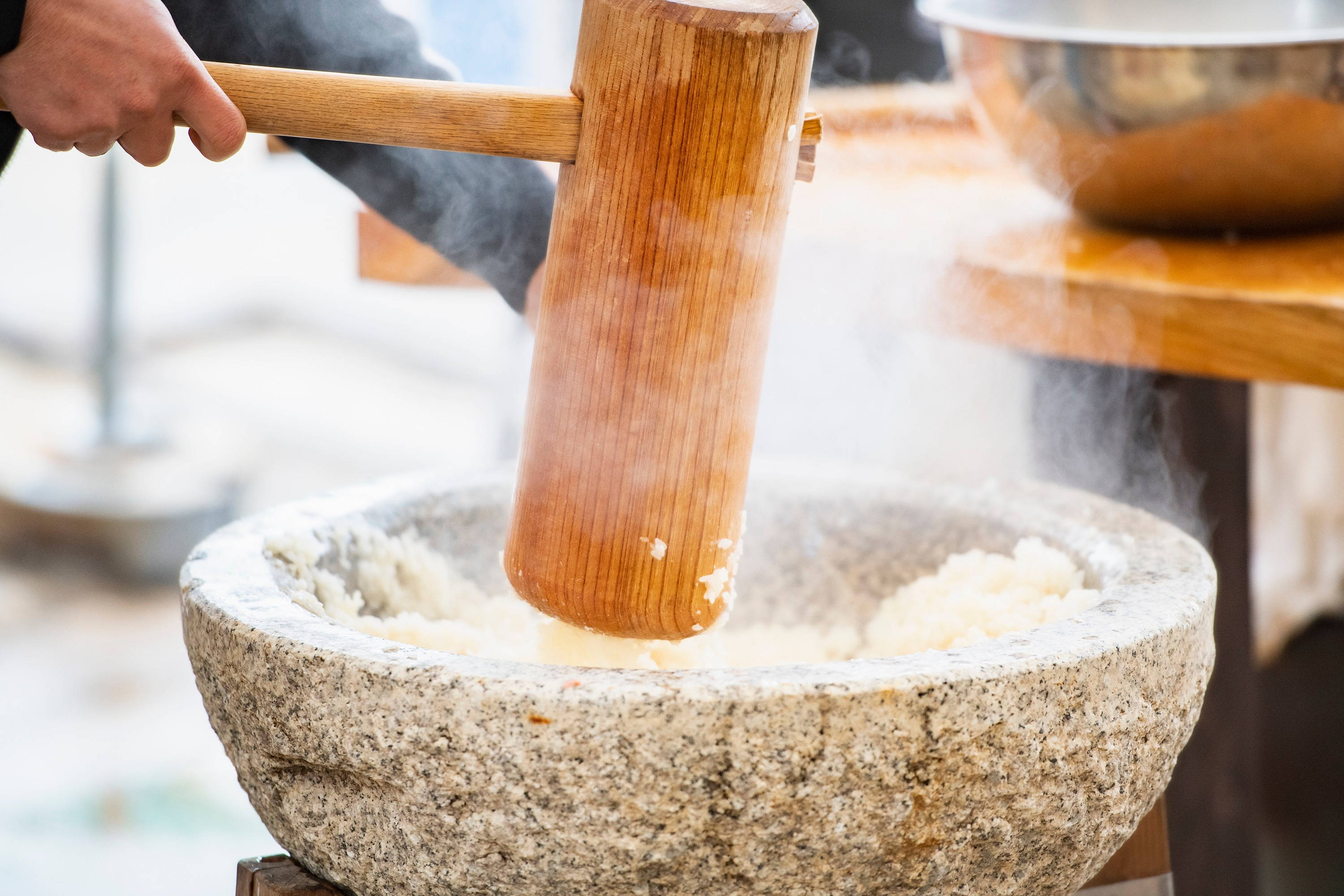 pounding steamed rice grains using mortar and pestle.