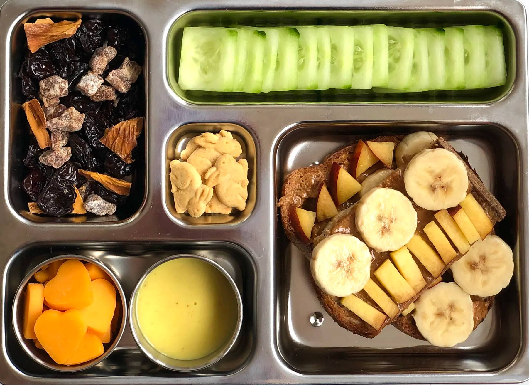 Sneak peek of a kid's quick and healthy school lunch containing Sourdough Toasts with Almond Butter, Banana, & Peaches, Trail Mix, English Cucumber Squares, Organic Honey Mustard Dressing, Cheddar Cheese Shapes, Mini Graham Crackers.