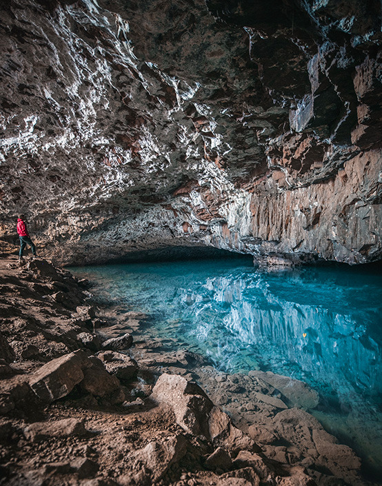 man in red jacket exploring underground river
