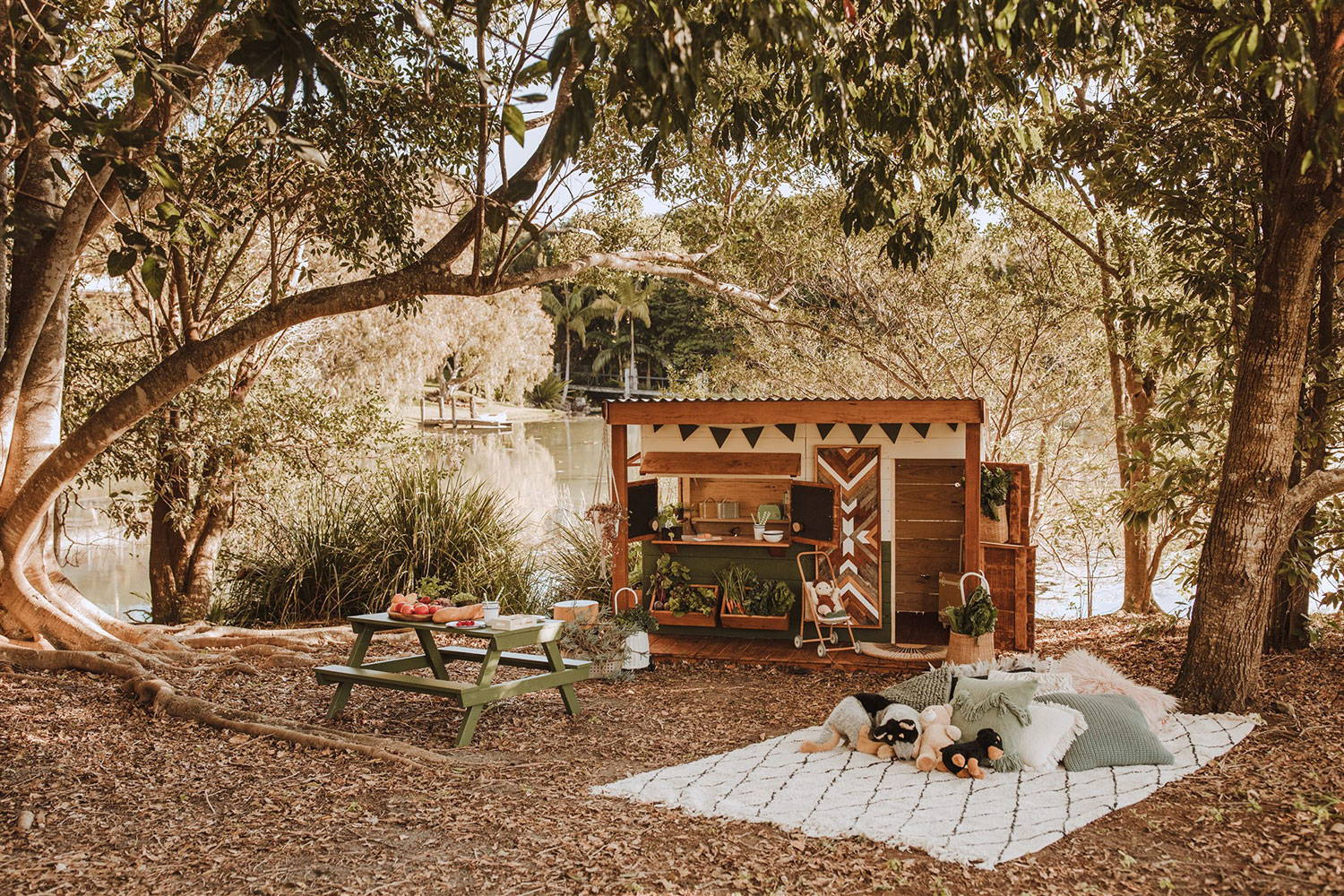 Timber cubby house with verandah and picnic table next to lake