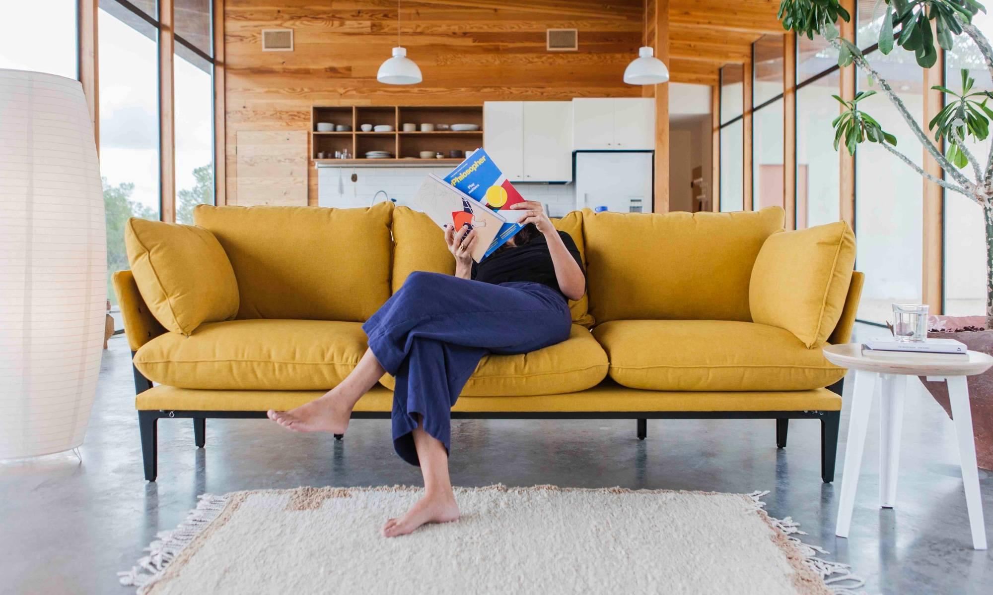 A woman reading on the Floyd sofa in saffron.