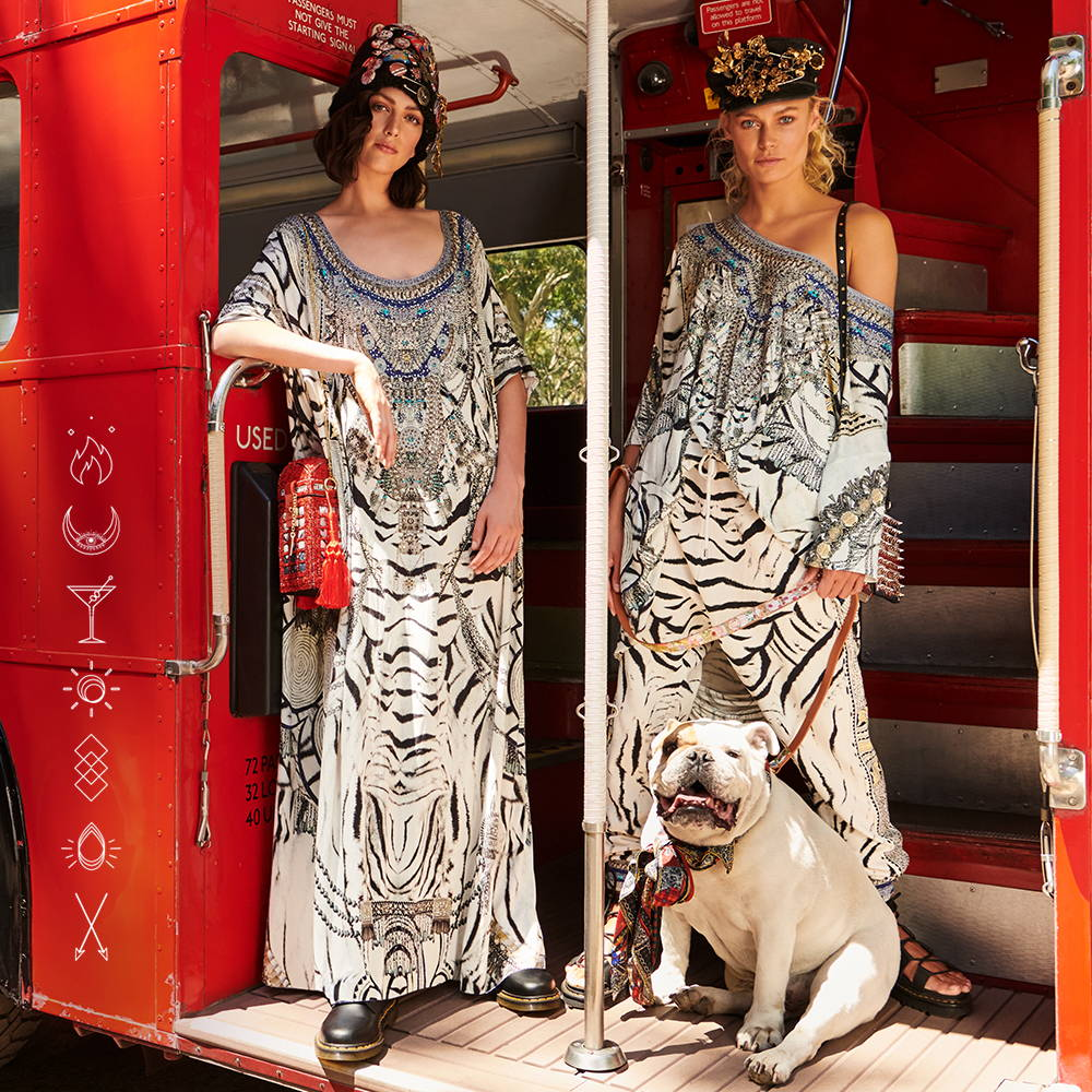 Models in red bus wearing CAMILLA black and hite kaftan, tee and pants.