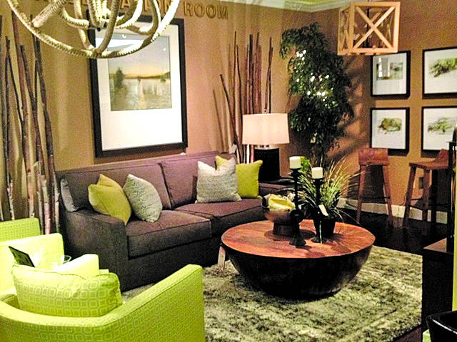 gray couch with green pillows in front of round coffee table with two green chairs next to it