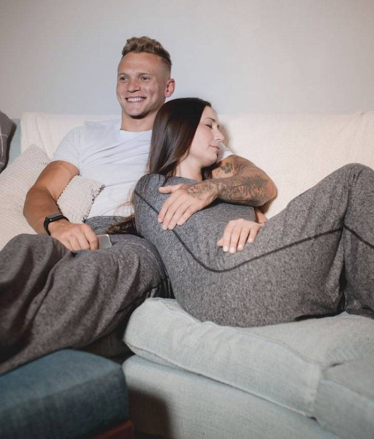 man and woman in sleep pod laying on couch watching tv