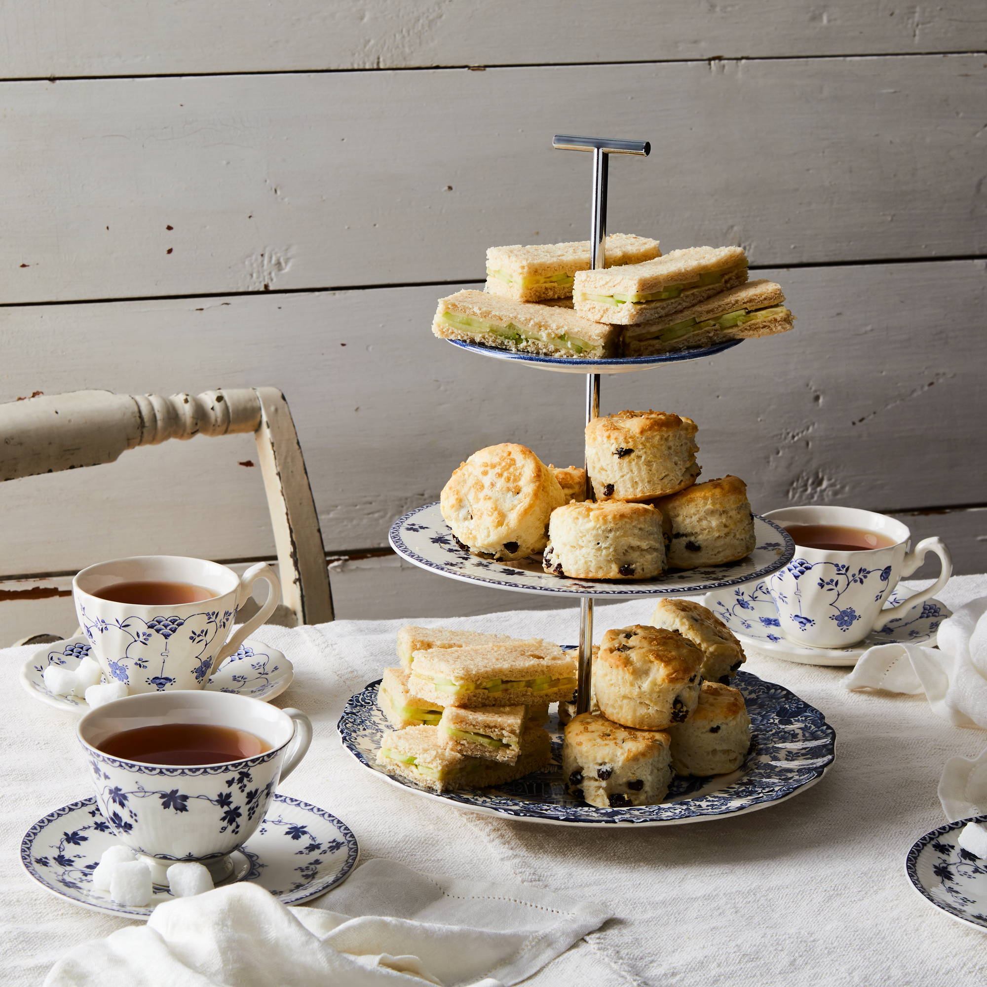 3-Tier cake stand with blue and white china piled high with tea sandwiches and biscuits plus teacups & saucers