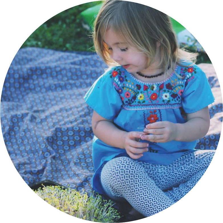 Toddler looking at a HAMAMA microgreen kit with fully grown microgreens.
