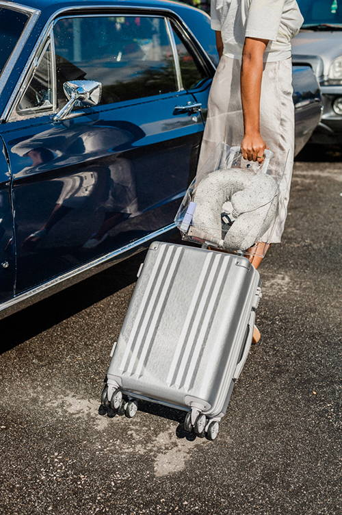 female model with rolling hardside silver CALPAK Ambeur carry on and silk travel set: neck pillow and eye mask