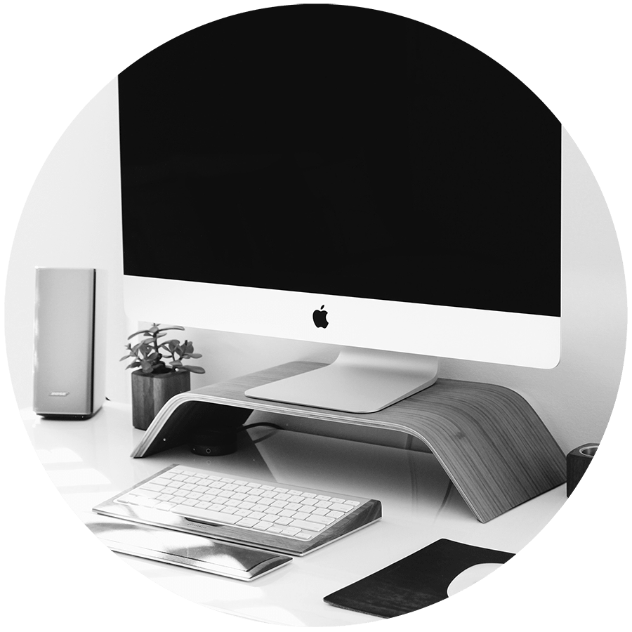 A Mac desktop monitor sitting on a wood stand