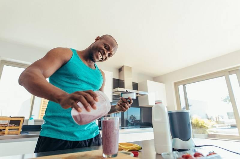 man making healthy protein shake in kitchen