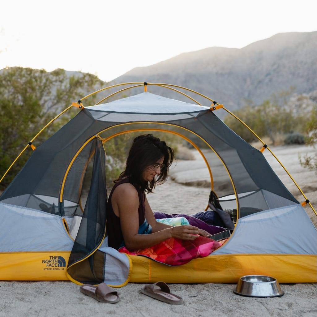 Person camping in Yosemite with North Face tent and Rumpl blanket