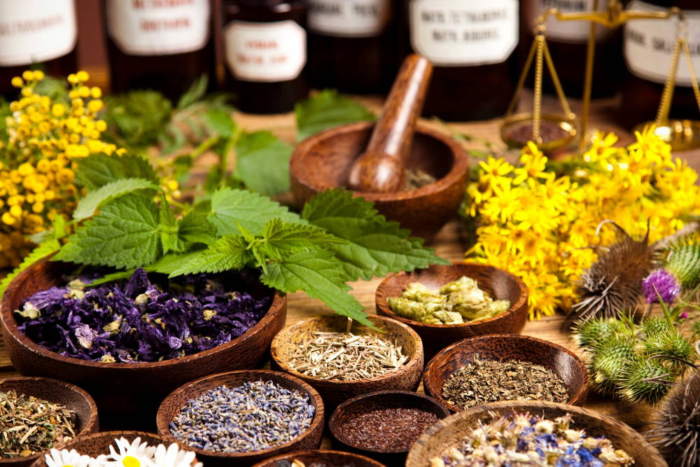 herbs and bottles on wooden table in bowls|build up your natural medicine cabinet