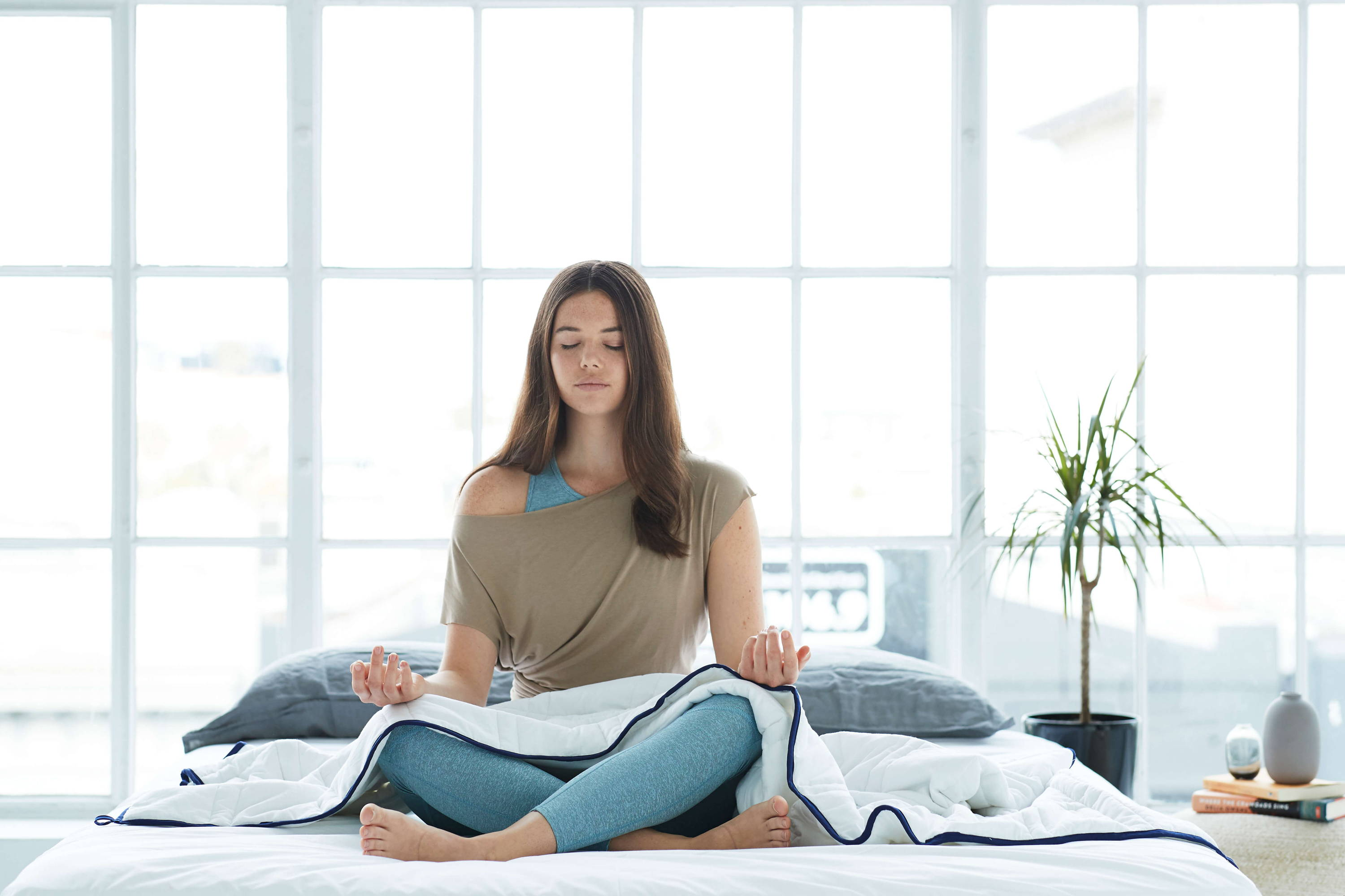 Girl meditating with Groundd Weighted Blanket